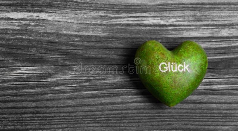 Πράσινη καρδιά με τη γερμανική λέξη για την τύχη στο γκρίζο ξύλινο υπόβαθρο στοκ εικόνα με δικαίωμα ελεύθερης χρήσης