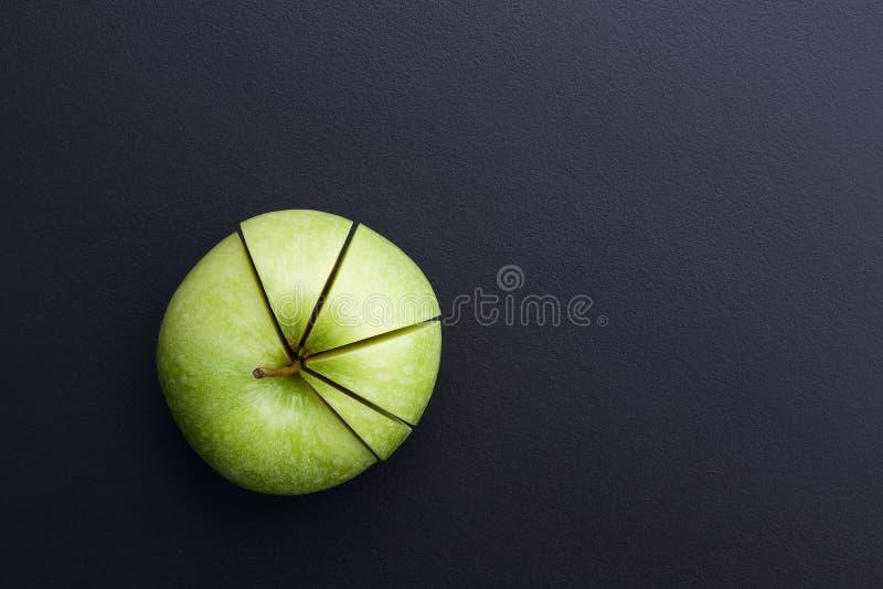 Πράσινη κοπή μήλων με μορφή του διαγράμματος πιτών στον πίσω πίνακα στοκ εικόνες με δικαίωμα ελεύθερης χρήσης