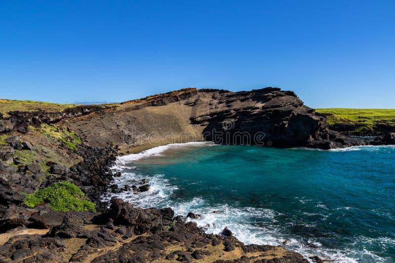 Πράσινη παραλία άμμου της Χαβάης Απότομος απότομος βράχος, γαλαζοπράσινο νερό, μπλε ουρανός Δύσκολη ακτή στο πρώτο πλάνο στοκ φωτογραφίες