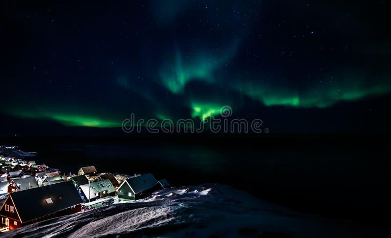 Πράσινη πυράκτωση της αυγής Borealis με τα λάμποντας αστέρια πέρα από το fjo στοκ εικόνες