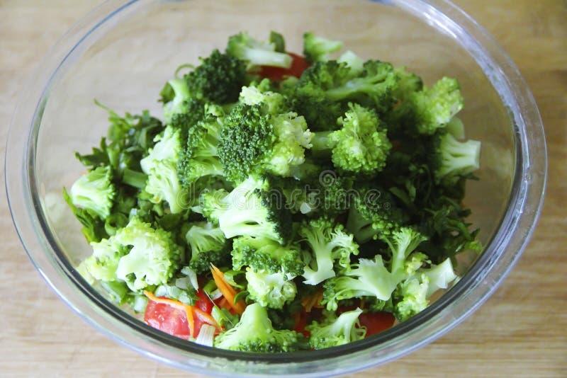 Πράσινη σαλάτα μπρόκολου σε ένα πιάτο γυαλιού σε ένα ξύλινο υπόβαθρο πινάκων στοκ εικόνα