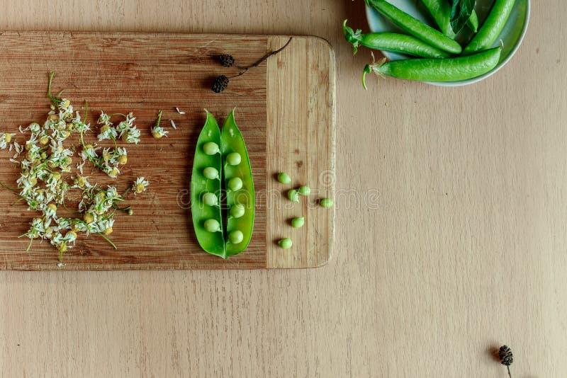 Πράσινη σειρά των μπιζελιών στην ξύλινη κουζίνα στοκ εικόνες