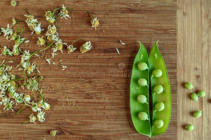 Πράσινη σειρά των μπιζελιών στην ξύλινη κουζίνα στοκ εικόνα