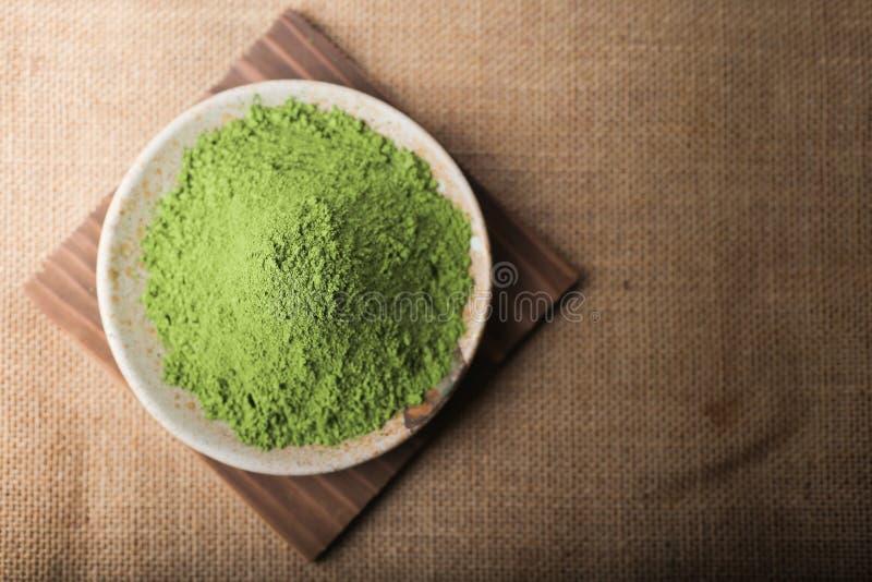 Πράσινη σκόνη τσαγιού στο πιάτο στον ξύλινο πίνακα στοκ φωτογραφία