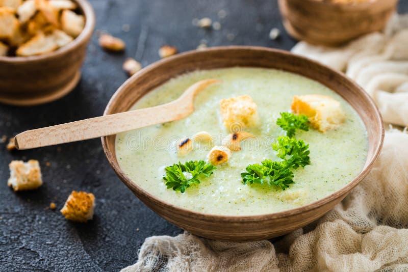 Πράσινη υγιής σούπα κρέμας με το μπρόκολο, κροτίδες, το δυτικό ανακάρδιο, μαϊντανός στοκ εικόνες