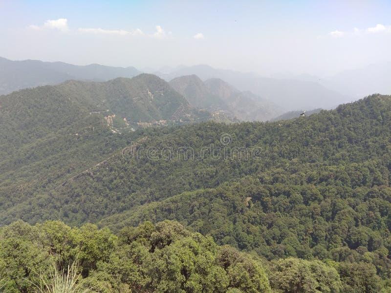 Πράσινοι δάσος και λόφοι με την πράσινη φύση με το μικρό χωριό στην περιοχή βουνών στοκ φωτογραφία