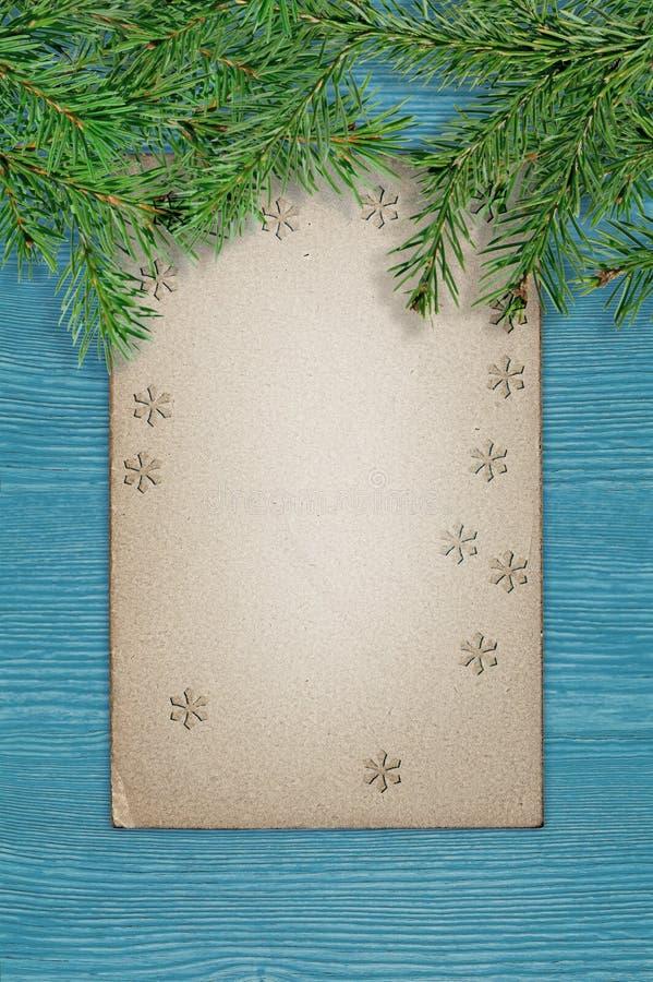 Πράσινοι κομψοί κλάδοι και παλαιό έγγραφο grunge για έναν μπλε ξύλινο πίνακα αφηρημένο ανασκόπησης Χριστουγέννων σκοτεινό διακοσμ στοκ εικόνα με δικαίωμα ελεύθερης χρήσης