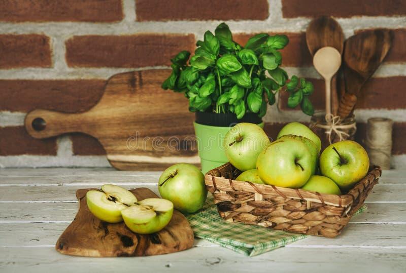 Πράσινοι μήλα και βασιλικός Freesh με τα ξύλινα στηρίγματα κουζινών στοκ εικόνα με δικαίωμα ελεύθερης χρήσης