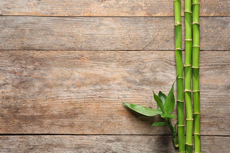 Πράσινοι μίσχοι και διάστημα μπαμπού για το κείμενο στο ξύλινο υπόβαθρο στοκ φωτογραφίες