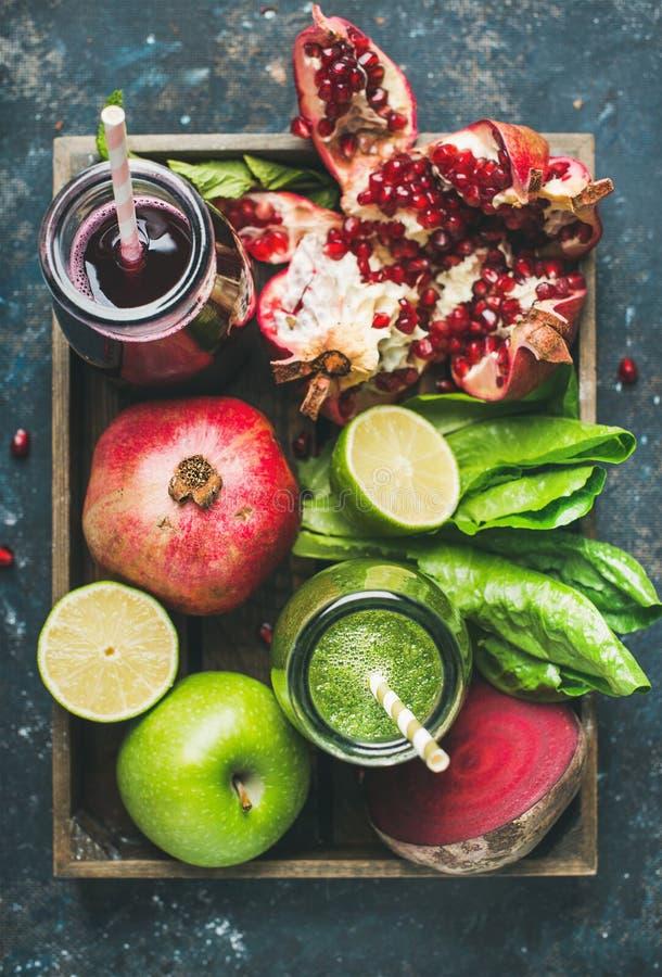 Πράσινοι, πορφυροί φρέσκοι χυμοί με τα φρούτα, πράσινα, λαχανικά στο δίσκο στοκ εικόνα
