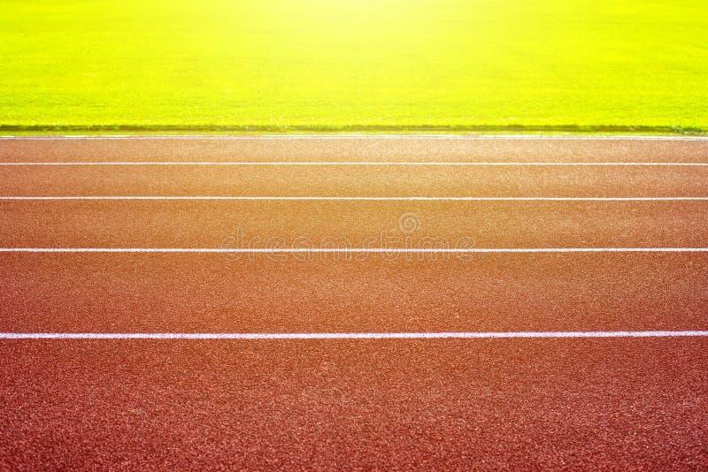 Πράσινος αγωνιστικός χώρος ποδοσφαίρου και κόκκινη τρέχοντας διαδρομή στο στάδιο στοκ εικόνα