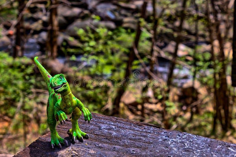 Πράσινος δεινόσαυρος Velociraptor με τα ξύλα στο υπόβαθρο στοκ φωτογραφίες με δικαίωμα ελεύθερης χρήσης