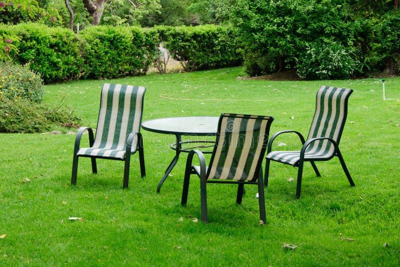 Πράσινος κήπος θερινών κατωφλιών με τη χλόη, τον πίνακα και τις καρέκλες στοκ φωτογραφία με δικαίωμα ελεύθερης χρήσης