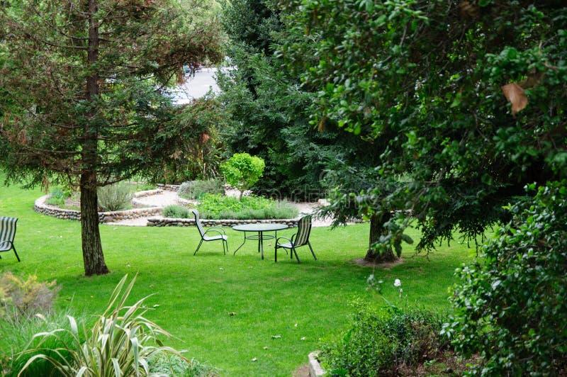 Πράσινος κήπος θερινών κατωφλιών με τη χλόη, τον πίνακα και τις καρέκλες στοκ εικόνα με δικαίωμα ελεύθερης χρήσης