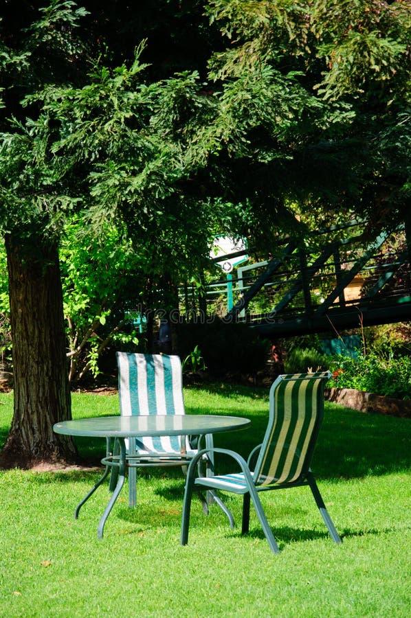 Πράσινος κήπος θερινών κατωφλιών με τη χλόη, τον πίνακα και τις καρέκλες στοκ φωτογραφίες