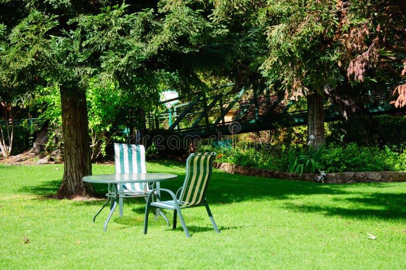 Πράσινος κήπος θερινών κατωφλιών με τη χλόη, τον πίνακα και τις καρέκλες στοκ φωτογραφία