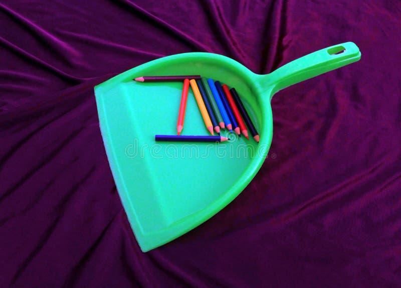 Πράσινος καθαριστής απορριμάτων με το μολύβι που απομονώνεται στο μαύρο υπόβαθρο στοκ εικόνες