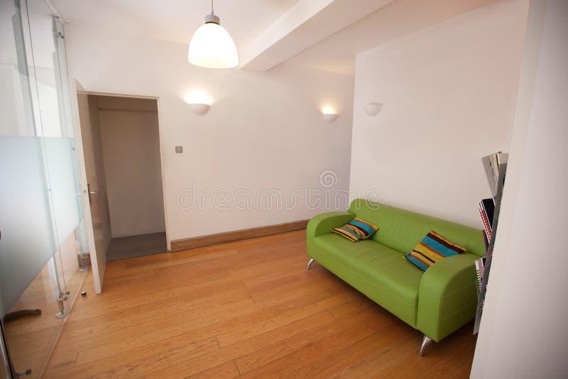 Πράσινος καναπές στο κενό γραφείο στοκ εικόνα με δικαίωμα ελεύθερης χρήσης