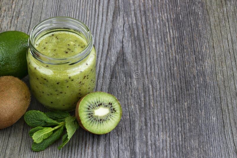 Πράσινος καταφερτζής με τα φρούτα, το αγγούρι, τη μέντα και το μαϊντανό ακτινίδιων στο ol στοκ εικόνες