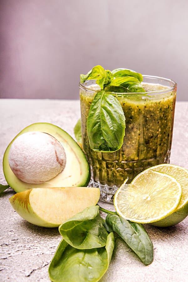 Πράσινος καταφερτζής του αβοκάντο, σπανάκι, βασιλικός, ασβέστης, πράσινο μήλο στο γκρίζο υπόβαθρο Υγιής έννοια eatin διατροφής στοκ φωτογραφίες