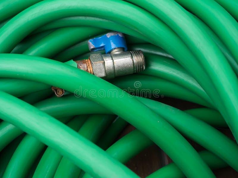 Πράσινος λαστιχένιος σωλήνας νερού με τη στρόφιγγα στοκ εικόνα με δικαίωμα ελεύθερης χρήσης