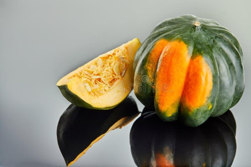 Πράσινος-πορτοκαλιά κολοκύθα κάστανων και μια τεμαχισμένη φέτα της κολοκύθας που βρίσκεται σε ένα γκρίζο υπόβαθρο στοκ φωτογραφία με δικαίωμα ελεύθερης χρήσης
