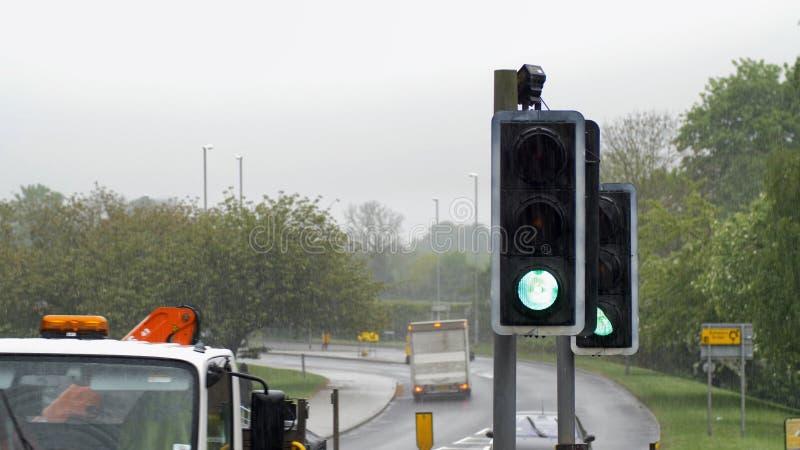Πράσινος φωτεινός σηματοδότης για τους πεζούς περάσματος στη βρετανική πόλη τη συννεφιάζω βροχερή ημέρα στοκ εικόνες