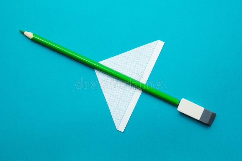 Πράσινο αεροπλάνο φιαγμένο από μολύβια και έγγραφο για ένα μπλε υπόβαθρο Παιδαριώδης φαντασία στοκ φωτογραφία με δικαίωμα ελεύθερης χρήσης