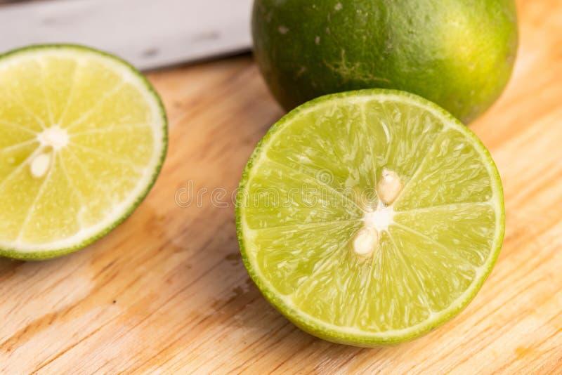 Πράσινο ασβέστιο και σπόρος με μαχαίρι σε ξύλινο σανίδα σε κουζίνα στοκ εικόνες