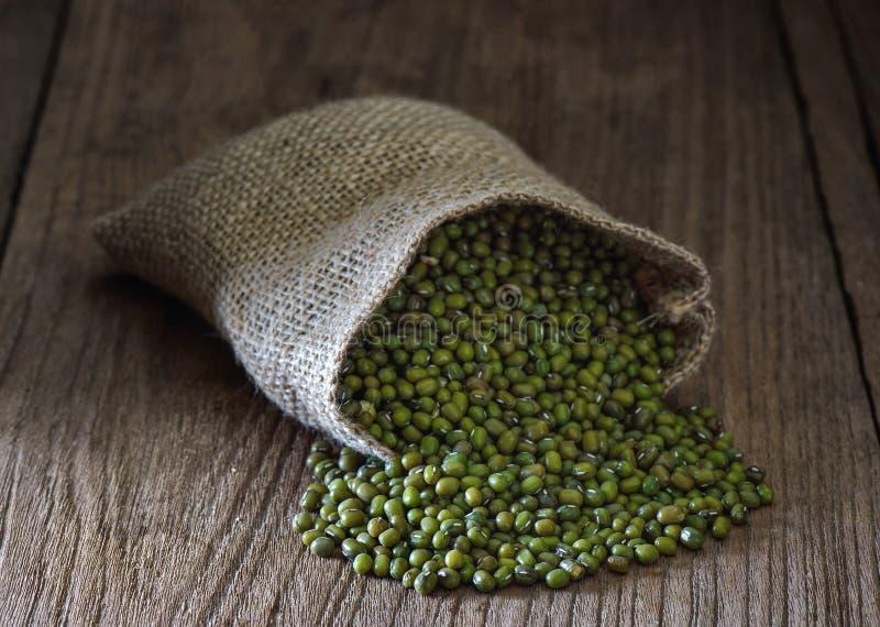 Πράσινο γραμμάριο ή mung φασόλι στους σάκους στον πίνακα στοκ εικόνες