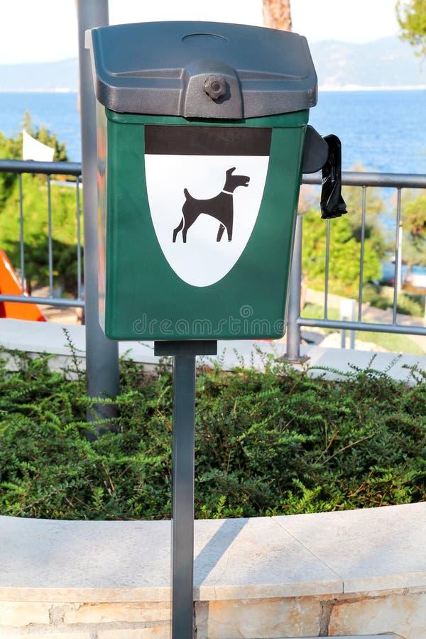 Πράσινο εμπορευματοκιβώτιο αποβλήτων σκυλιών σύνθετο σε έναν κοντινό τουριστών η θάλασσα/το δημόσιο δοχείο απορριμμάτων για το ση στοκ εικόνα με δικαίωμα ελεύθερης χρήσης