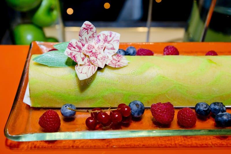 Πράσινο κέικ ελβετικών ρόλων τσαγιού στο πιάτο γυαλιού με τα φρέσκα μούρα, rasb στοκ φωτογραφία