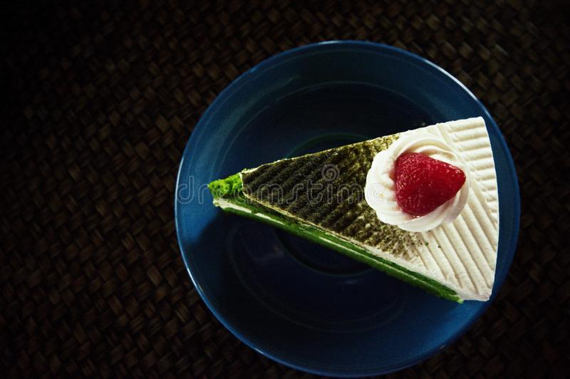 Πράσινο κέικ τσαγιού που τοποθετείται σε ένα μπλε πιάτο στοκ φωτογραφίες με δικαίωμα ελεύθερης χρήσης