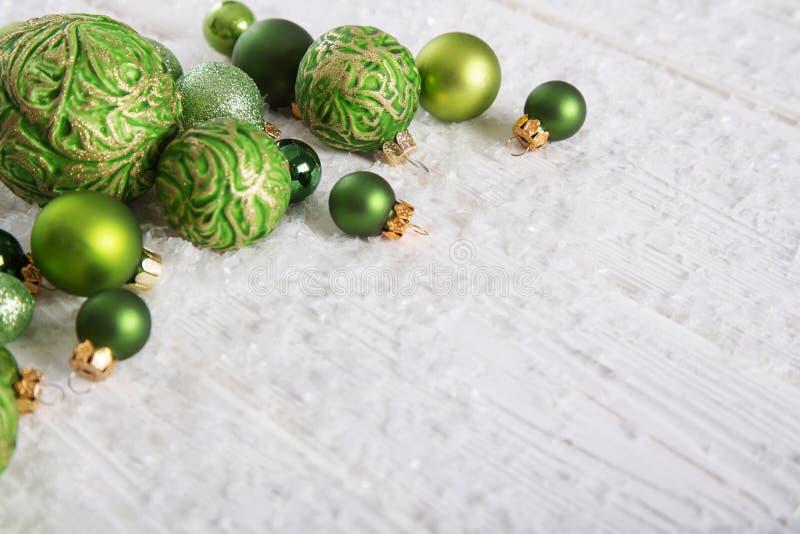Πράσινο και άσπρο υπόβαθρο Χριστουγέννων με το χιόνι και σφαίρες για το Δεκέμβριο στοκ εικόνες
