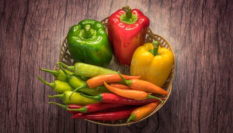 Πράσινο και κόκκινο πιπέρι κουδουνιών καψικού στο ξύλινο υπόβαθρο στοκ εικόνες