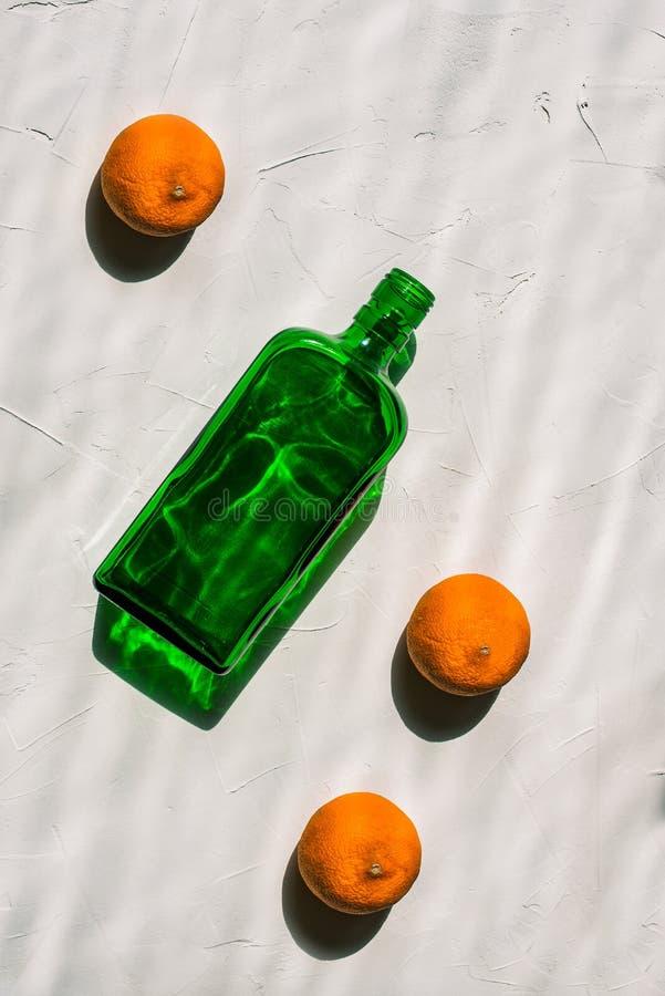 Πράσινο κενό μπουκάλι και τρία μανταρίνια σε ένα άσπρο υπόβαθρο Ελάχιστη ακόμα ζωή Φωτεινές ελαφριές, σκληρές σκιές και μια ανταν στοκ φωτογραφία