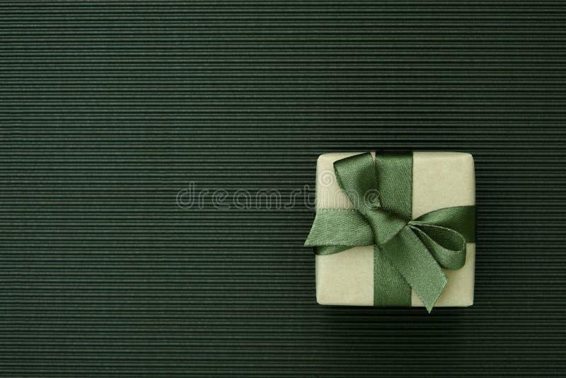 Πράσινο κιβώτιο δώρων που τυλίγεται στο έγγραφο τεχνών για το ριγωτό υπόβαθρο χαρτονιού στοκ εικόνες