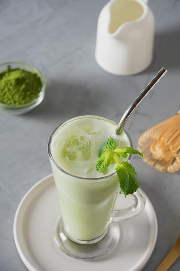 Πράσινο κρύο τσάι matcha στο γυαλί latte με τον κύβο πάγου και γάλα στον γκρίζο πίνακα o E στοκ φωτογραφία με δικαίωμα ελεύθερης χρήσης