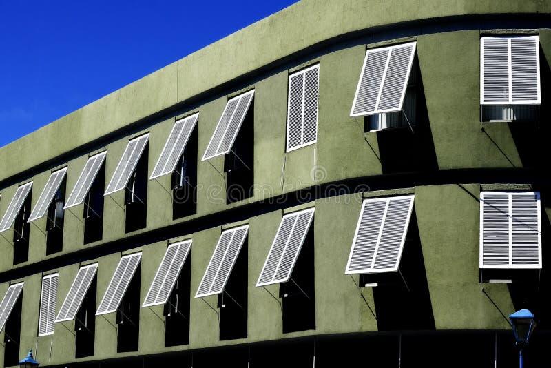 Πράσινο κτήριο με τα άσπρα παράθυρα στοκ φωτογραφία