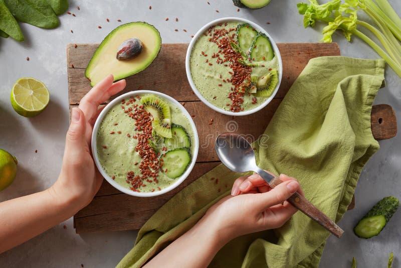 Πράσινο κύπελλο καταφερτζήδων με το φρέσκα ακτινίδιο, flaxseeds, το αγγούρι και το αβοκάντο στα θηλυκά χέρια στοκ φωτογραφίες