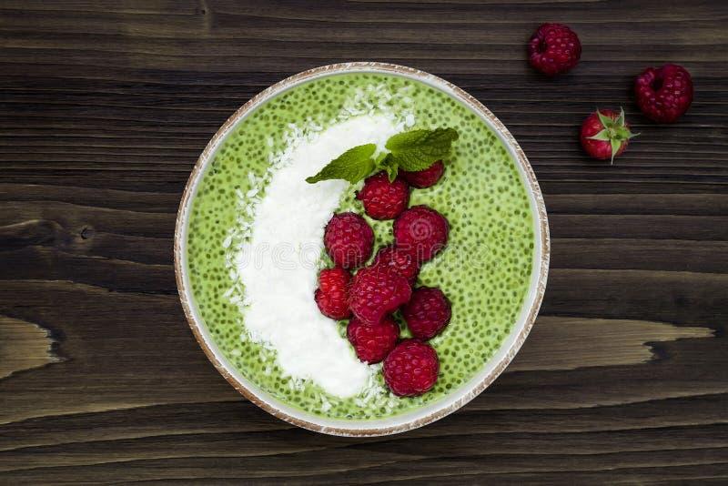 Πράσινο κύπελλο πουτίγκας σπόρου chia τσαγιού Matcha, vegan επιδόρπιο με το σμέουρο και γάλα καρύδων Η υπερυψωμένη, τοπ άποψη, επ στοκ εικόνες με δικαίωμα ελεύθερης χρήσης