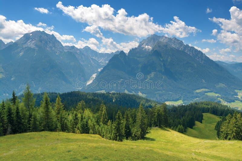 Πράσινο λιβάδι, κορυφογραμμή βουνών κάτω από το μπλε ουρανό στοκ εικόνα με δικαίωμα ελεύθερης χρήσης