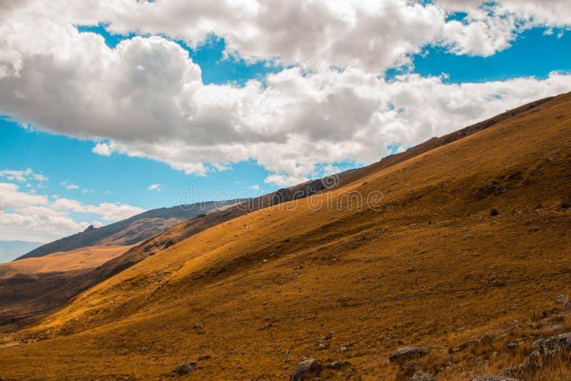 Πράσινο λιβάδι με έναν όμορφο νεφελώδη ουρανό μεγάλα βουνά βουνών τοπίων στοκ εικόνες
