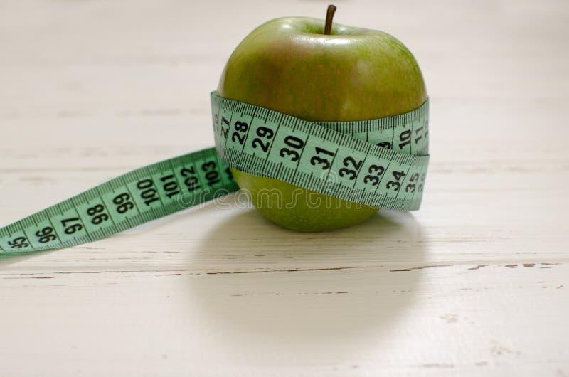 Πράσινο μήλο που τυλίγεται στο εκατοστόμετρο στο άσπρο ξύλινο πνεύμα υποβάθρου στοκ φωτογραφία με δικαίωμα ελεύθερης χρήσης