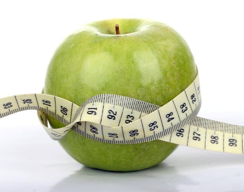 Πράσινο μήλο με ένα μέτρο ταινιών στοκ εικόνες