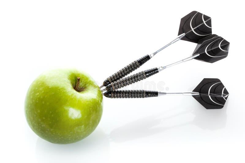 Πράσινο μήλο ως στόχο για τα μαύρα βέλη χάλυβα στοκ φωτογραφία με δικαίωμα ελεύθερης χρήσης