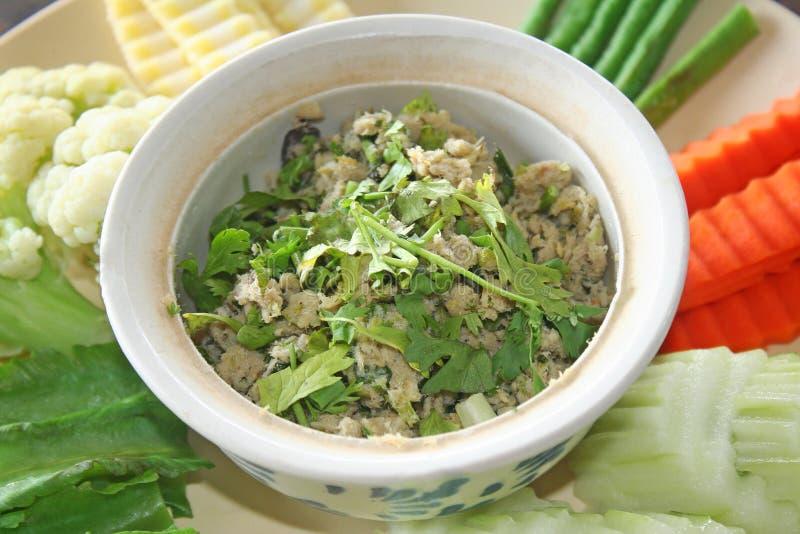 Πράσινο μίγμα εμβύθισης τσίλι με το σύνολο ψημένων στη σχάρα ψαριών και φρέσκων λαχανικών στοκ φωτογραφία
