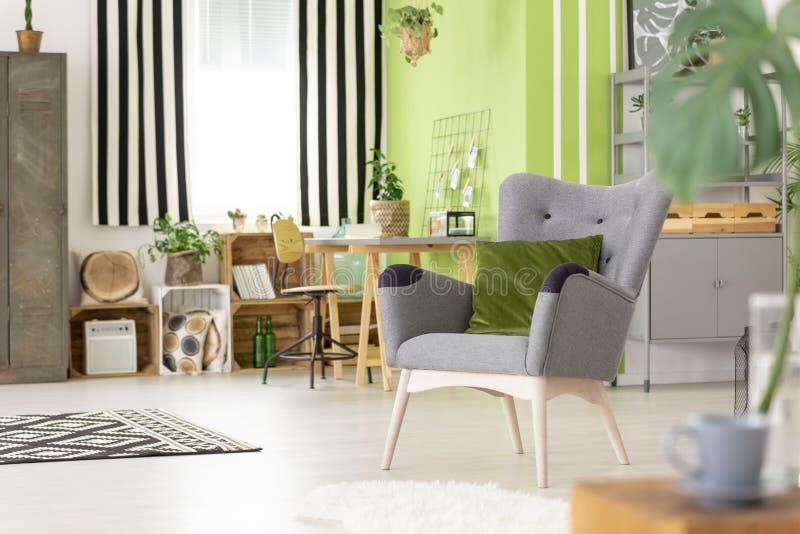 Πράσινο μαξιλάρι στην γκρίζα πολυθρόνα στο σύγχρονο εσωτερικό πνεύμα καθιστικών στοκ φωτογραφίες με δικαίωμα ελεύθερης χρήσης