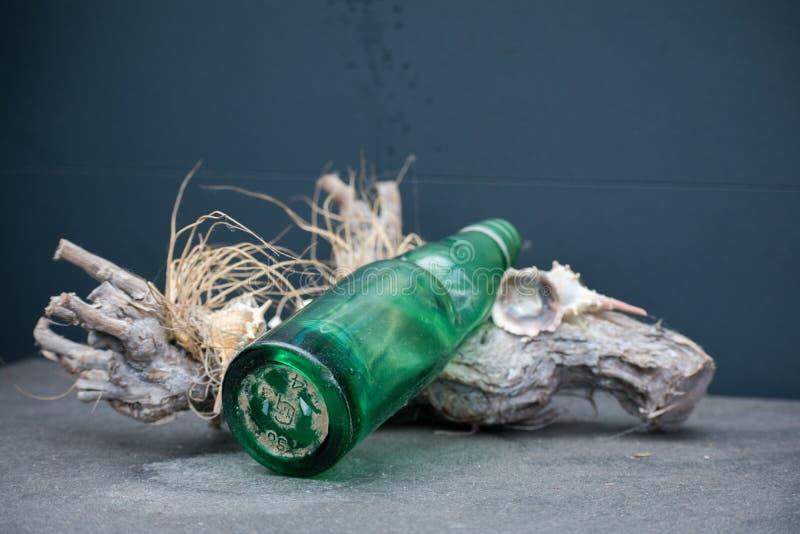 Πράσινο μπουκάλι γυαλιού σε ένα κομμάτι του ξύλου με τη θερινή παραλία Β κοχυλιών στοκ φωτογραφίες με δικαίωμα ελεύθερης χρήσης