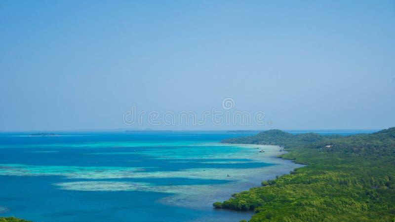 Πράσινο νησί και μπλε ακτή οριζόντων θάλασσας νερού τυρκουάζ με το σαφή ουρανό στο jawa karimun στοκ εικόνα